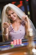 Woman in bridal veil in casino playing roulette and smiling (selective focus) - stock photo
