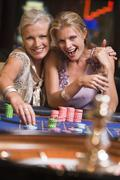 Two women in casino playing roulette and smiling (selective focus) Stock Photos