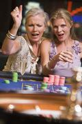 Two women in casino playing roulette and smiling (selective focus) - stock photo