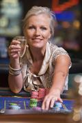 Woman in casino playing roulette and smiling (selective focus) - stock photo