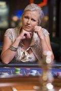 Woman in casino playing roulette and thinking (selective focus) - stock photo