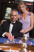 Couple in casino playing roulette and smiling (selective focus) - stock photo