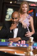 Couple in casino playing roulette (selective focus) - stock photo