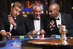 Three men in casino playing roulette and smiling (selective focus) - stock photo