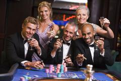 Five people in casino playing roulette and smiling (selective focus) - stock photo