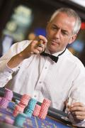 Man in casino playing roulette and smoking cigar (selective focus) Stock Photos