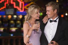 Couple in casino with cigar and champagne smiling (selective focus) - stock photo