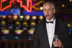 Man in casino with cigar and champagne (selective focus) - stock photo