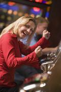 Woman in casino excited playing slot machine with people in background - stock photo