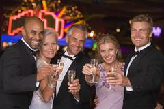 Five people in casino with champagne smiling (selective focus) - stock photo