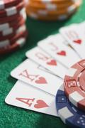 Playing cards making royal flush in hearts by poker chips (close up/selective Stock Photos