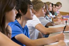 Students in class paying attention and taking notes (selective focus) Stock Photos
