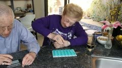 Elderly Couple, wife struggles opening pill bottle Stock Footage