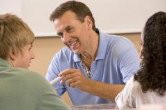 Opettaja kaksi opiskelijaa luokkahuoneessa Kuvituskuvat