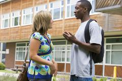 Two students standing outdoors talking Stock Photos