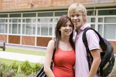 Two students standing outdoors with arms around waists smiling Stock Photos