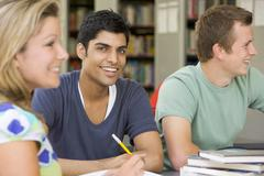 Stock Photo of Three people in library studying (selective focus)