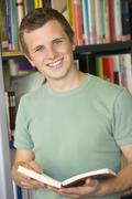 Man in library holding book Stock Photos