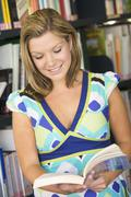 Woman in library holding book (selective focus) Stock Photos