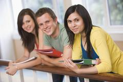 Three students in corridor leaning on railing (depth of field) - stock photo