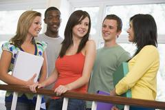 Five students in corridor leaning on railing with notebooks Stock Photos