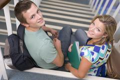 Two students sitting on staircase with notebooks (selective focus) Stock Photos