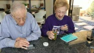 Elderly Couple Woman organizes pills with techie elderly husband on iPhone Stock Footage