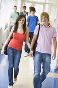 Two students walking in corridor holding hands with students in background Stock Photos