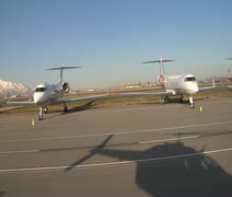 Shadow of helicopter passing by private jets Stock Footage