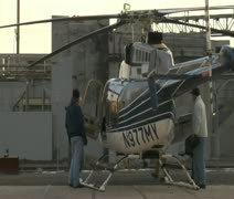 Men inspect stationary helicopter Stock Footage
