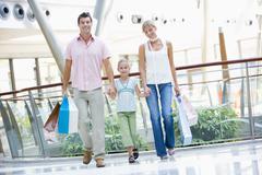 Äiti ja isä kanssa nuori tytär klo ostoskeskuksessa Kuvituskuvat