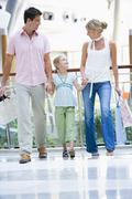 Mother and father with young daughter at a shopping mall - stock photo
