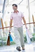Man with shopping bags at a shopping mall - stock photo