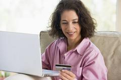 Woman with a laptop computer making an online purchase with credit card Stock Photos