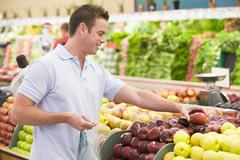 Man shopping for apples at a grocery store - stock photo