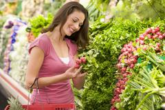 Woman shopping for beets at a grocery store - stock photo