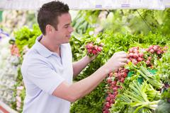 Man shopping for beets at a grocery store - stock photo