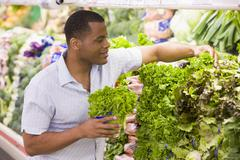 Man shopping for lettuce at a grocery store Stock Photos