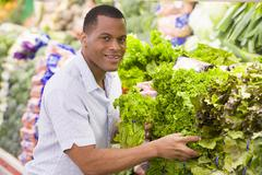 Man shopping for lettuce at a grocery store - stock photo