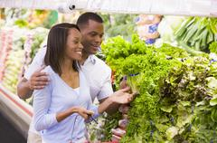 Young couple shopping for lettuce at a grocery store Stock Photos