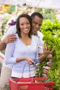 Young couple shopping for lettuce at a grocery store - stock photo