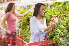 Women shopping for vegetables at a grocery store Stock Photos