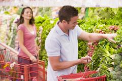 Young couple shopping for vegetables at a grocery store Stock Photos