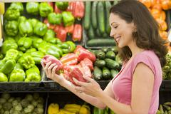 Woman shopping for bell peppers at a grocery store Stock Photos
