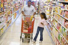 Isä ja tytär ostoksilla ruokakaupassa Kuvituskuvat