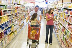 Mother and father with young daughter shopping at the grocery store. - stock photo