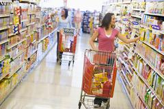 Two women shopping at a grocery store Stock Photos