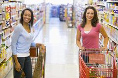 Two women talking to each other at a grocery store - stock photo