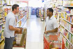 Two men talking to each other at a grocery store Stock Photos