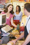 Stock Photo of Women paying for purchases at a grocery store